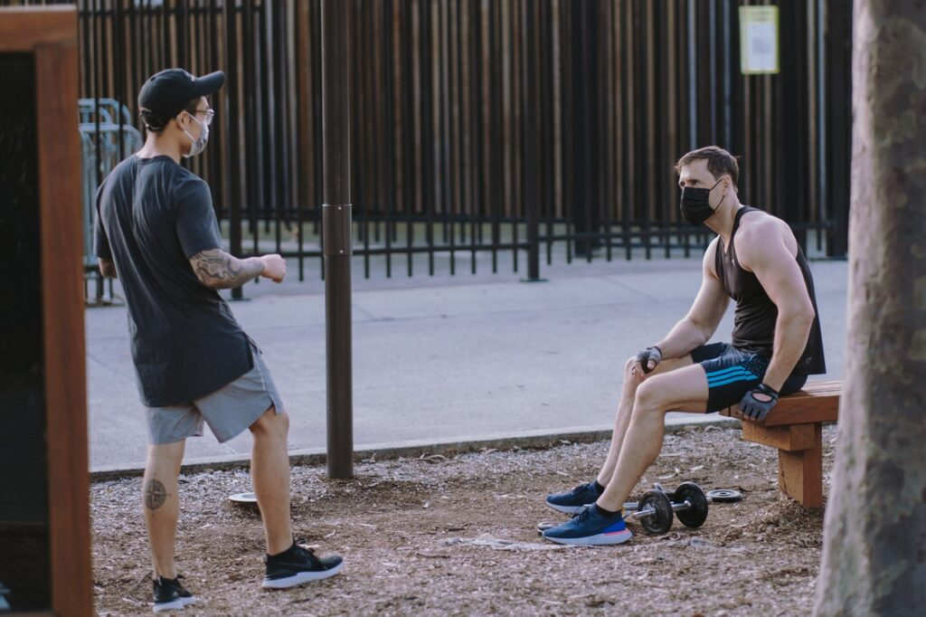 two men talking and doing workout