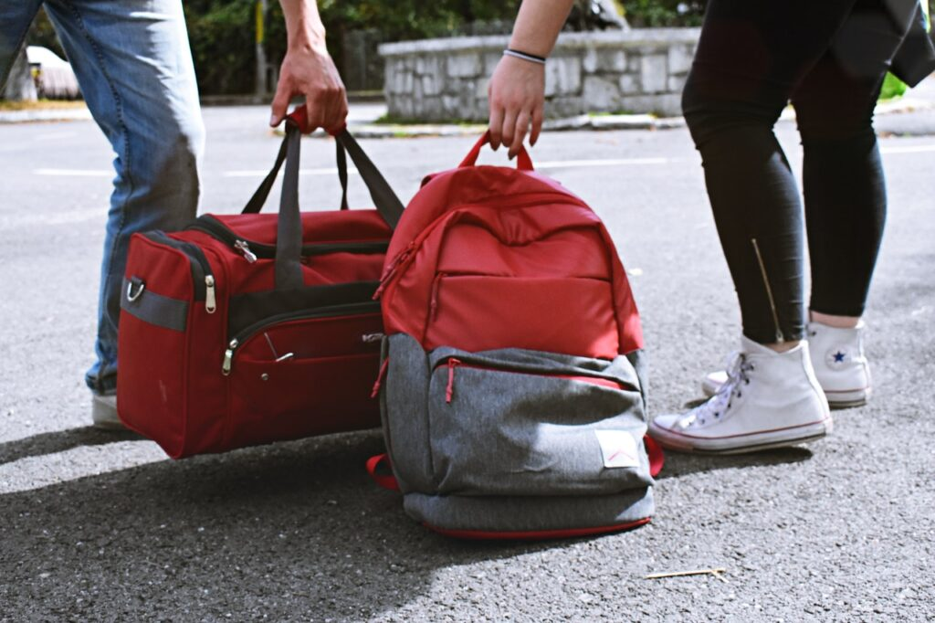 two person carrying red backpack