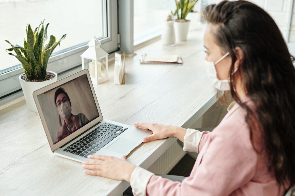 woman wearing mask front laptop