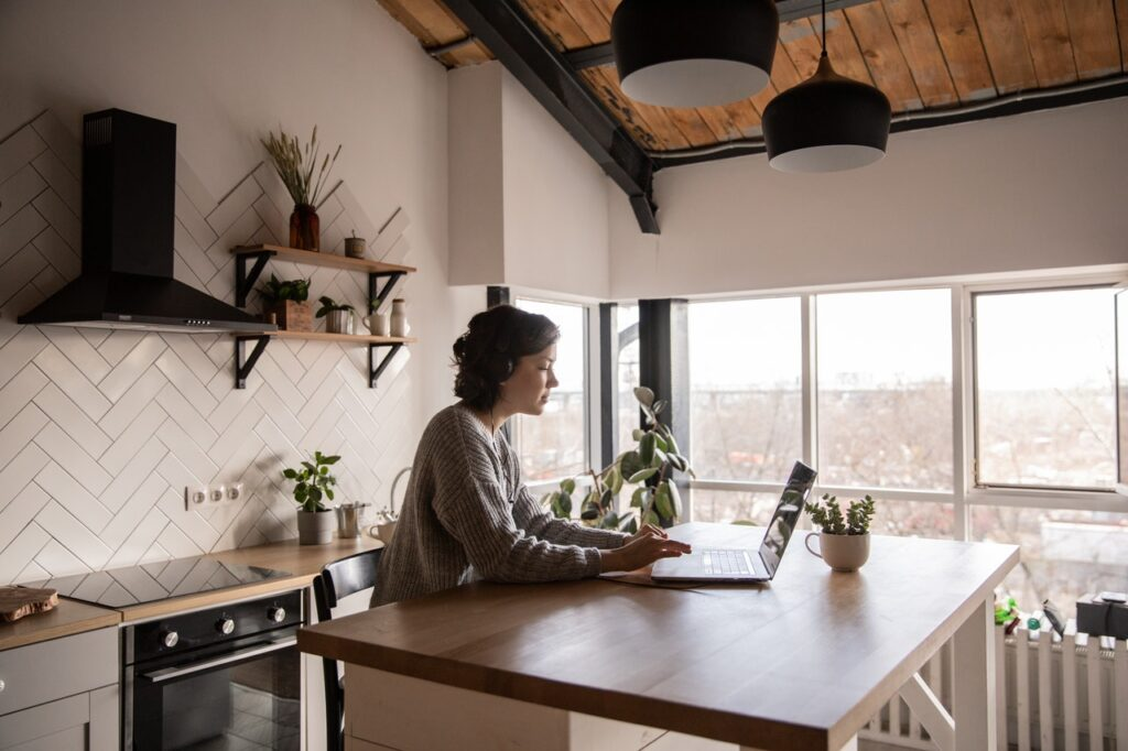 young-woman-surfing-laptop-in-kitchen