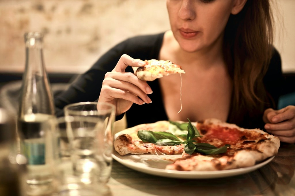 woman holds sliced pizza