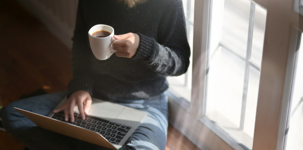 woman using laptop while holding a cup of coffee